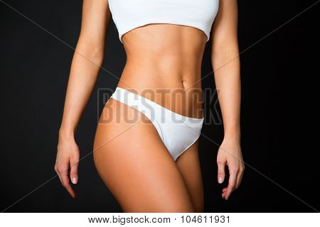 Slim Tanned Woman's Body. Isolated Over Black Background.