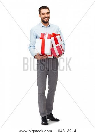people, christmas, birthday and holidays concept - happy young man holding gift boxes