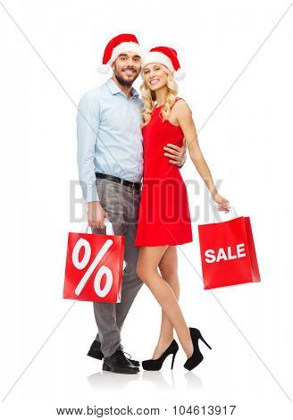 christmas, people, sale, discount and holidays concept - happy couple in santa hats hugging with red shopping bags