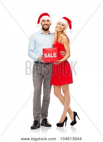 christmas, people, sale, discount and holidays concept - happy couple in santa hats with red sale sign