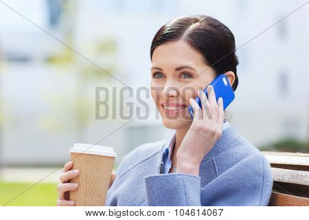business and people concept - young smiling woman calling on smartphone and drinking coffee in city