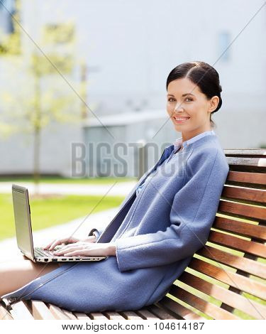 business, technology and people concept - young smiling woman with laptop computer sitting on bench in city