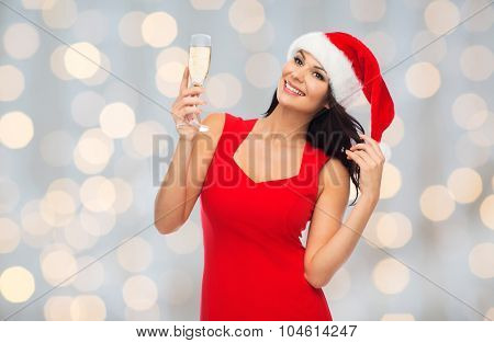 people, holidays, christmas and celebration concept - beautiful sexy woman in santa hat and red dress with champagne glass over lights background