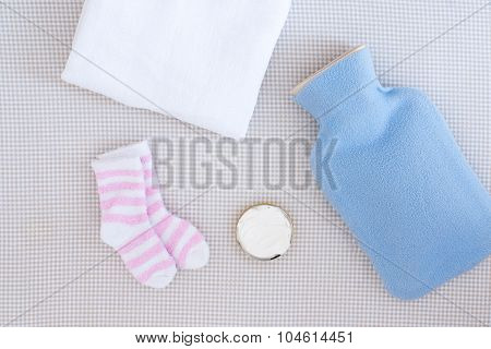 Hot Water Bottle And Little Baby Socks - Studio Shot From Above