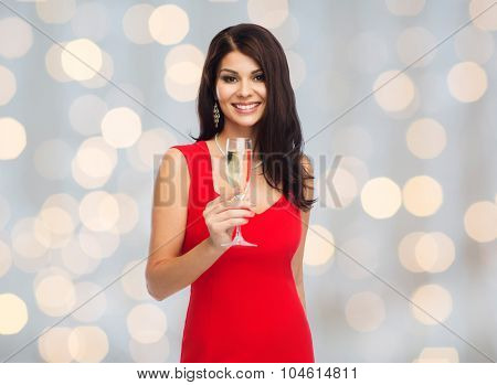 people, holidays, christmas and celebration concept - beautiful sexy woman in red dress with champagne glass over lights background