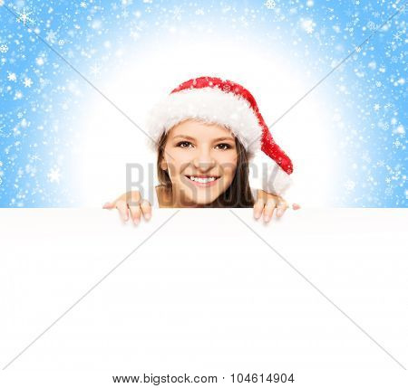 Young and attractive teenager girl with a blank billboard over blue background with snow flakes