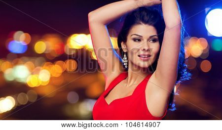 people, holidays, disco, nightlife and leisure concept - beautiful sexy woman in red dress dancing over night street lights background