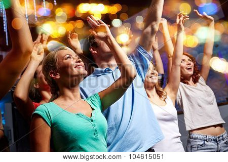party, holidays, celebration, nightlife and people concept - smiling friends waving hands at concert in club