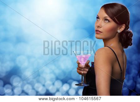 party, drinks, holidays, luxury and celebration concept - smiling woman in evening dress holding cocktail over blue lights background