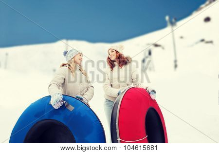 winter, leisure, sport, friendship and people concept - happy girl friends with snow tubes outdoors over mountain background