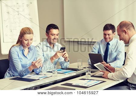 business, people and technology concept - smiling business team with smartphone and papers meeting in office