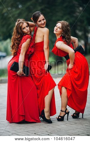 portrait of a three beautiful girl bridesmaid in red dress posing