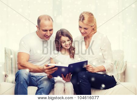 family, leisure, education and people - smiling mother, father and little girl reading book over snowflakes background