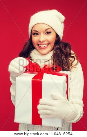 christmas, x-mas, winter, happiness concept - smiling woman in white clothes with gift box