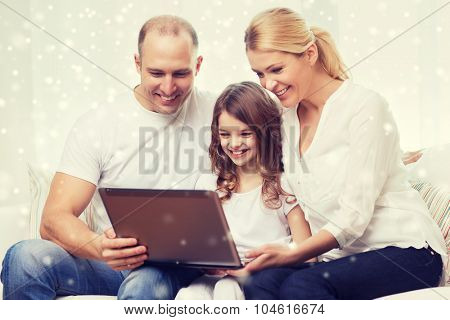 family, childhood, technology and people concept - smiling family with laptop computer over snowflakes background