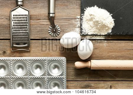 Kitchen utensils and ingredients for homemade pasta ravioli on wooden table