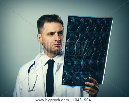 Medical doctor with MRI spinal scan portrait against grey background