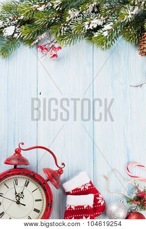 Christmas wooden background with snow fir tree, alarm clock and decor. View with copy space