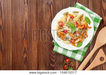 Colorful penne pasta with tomatoes and basil on wooden table. Top view with copy space