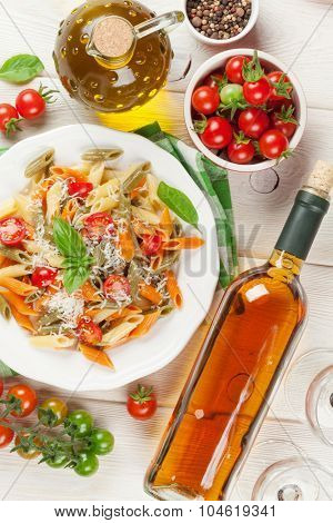 Colorful penne pasta and white wine on wooden table. Top view