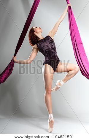 Beautiful ballet-dancer, modern style dancer posing on studio background