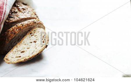 Freshly baked traditional bread on white marble background