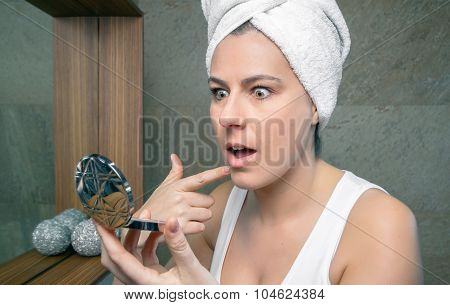 Surprised woman looking an acne pimple in mirror