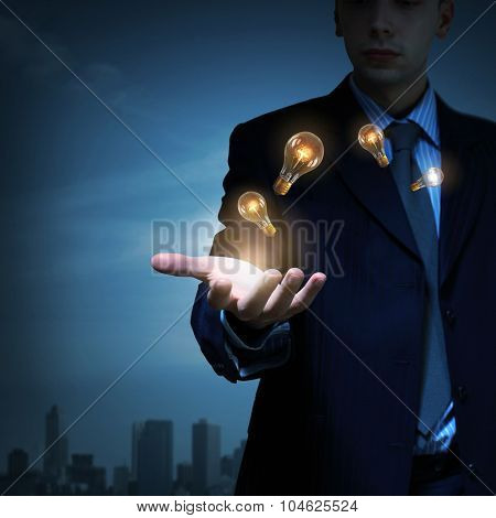 Businessman presenting glass glowing light bulb in his hand