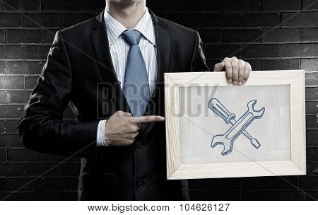 Unrecognizable businessman holding chalkboard with tools for success concept