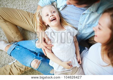 Ecstatic girl and her parents enjoying weekend at home