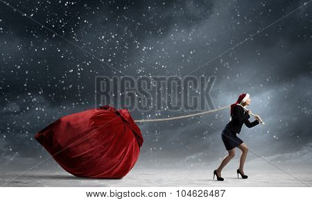 Santa woman pulling huge red gifts bag