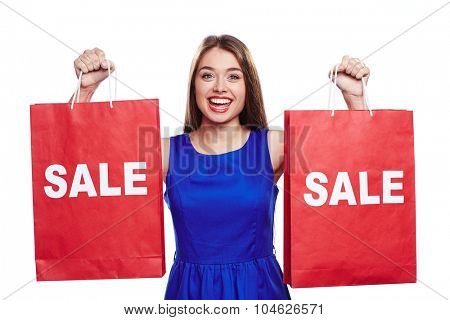 Happy woman with red paperbags announcing sale