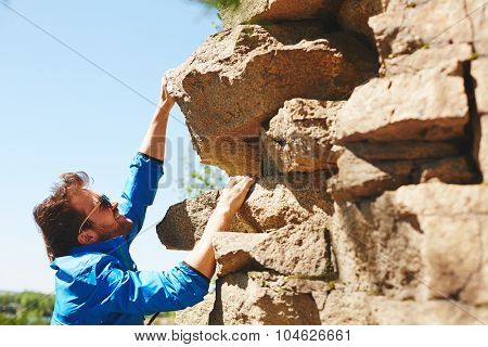 Active guy in sportswear climbing on top of rock