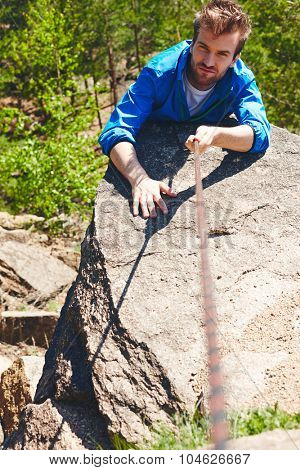 Young sportsman ascending cliff of mountain