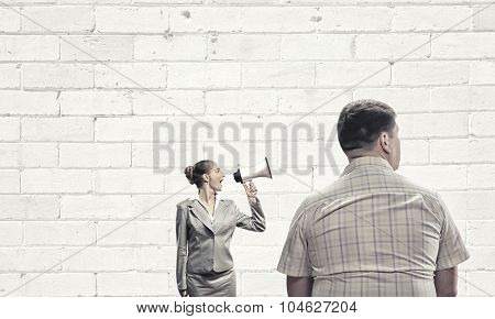 Furious woman screaming agressively in megaphone at man