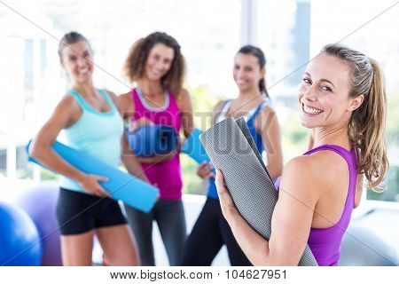 Portrait of a cheerful woman holding exercise mat in fitness studio