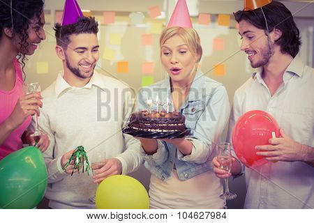 Businesswoman blowing birthday candles while colleagues looking at her in creative office