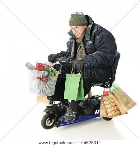 A bundled senior man intensely driving his Christmas gift-laden scooter.  On a white background.