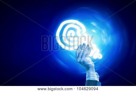 Close up of human hand holding light bulb in palm