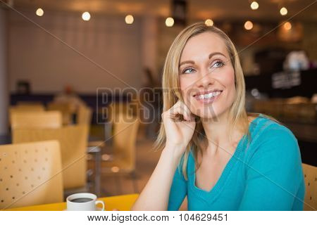Happy thoughtful young woman looking away at table in cafe