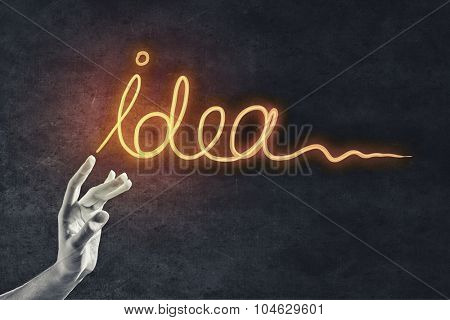 Person hand touching with fingers glowing idea word