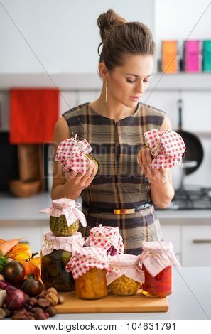 Woman In Kitchen Holding Preserves And Looking At Jars
