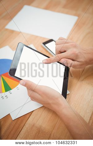 Cropped hand of man using digital tablet while papers on desk in office