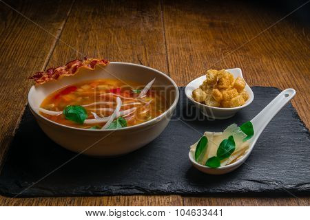 Vegetable soup served with crisp bacon, cheese and croquettes