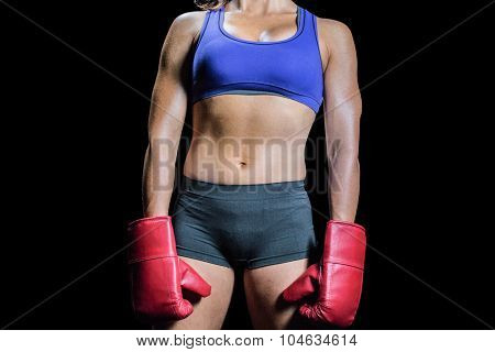 Midsection of female boxer with gloves against black background