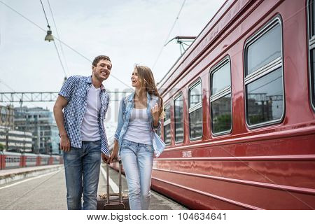 Smiling couple with a suitcase at the train
