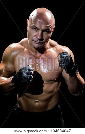 Portrait of muscular man with fighting stance against black background