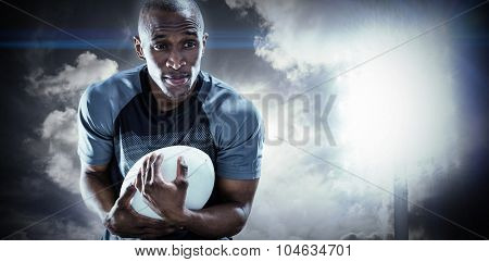Rugby player smiling while catching ball against spotlight in sky