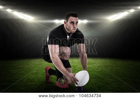 Rugby player getting ready to kick ball against rugby stadium