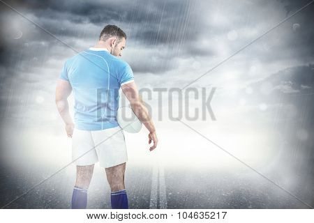 Rugby player standing with ball against cloudy sky